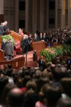 Congregation stands as the First Presidency enters