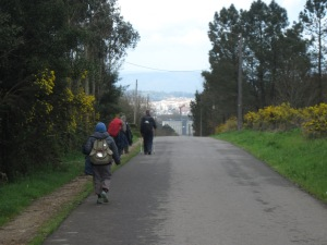 An early glimpse of Santiago as we rounded the hill -- Ronan walking ahead.