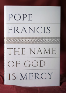"A reproduction of the front page of Pope Francis's book ""The name of God is Mercy"" is seen in this Thursday, Jan. 7, 2016 photo taken in Rome, Italy. This is the first time the Pope has put his name on a book since he was elected. It's a book-length conversation with an Italian journalist, focusing on mercy, the real leitmotiv of his papacy and the Holy Year. (AP Photo/Andrew Medichini)"