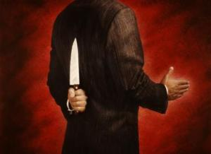 BUSINESSMAN WITH KNIFE BEHIND BACK